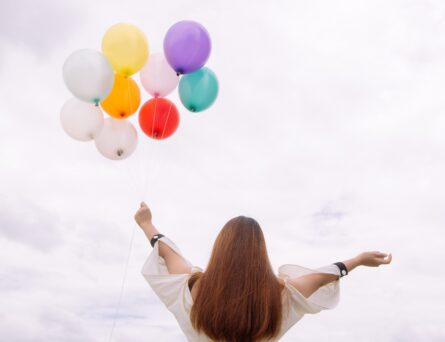 Mujer alzando globos al cielo.